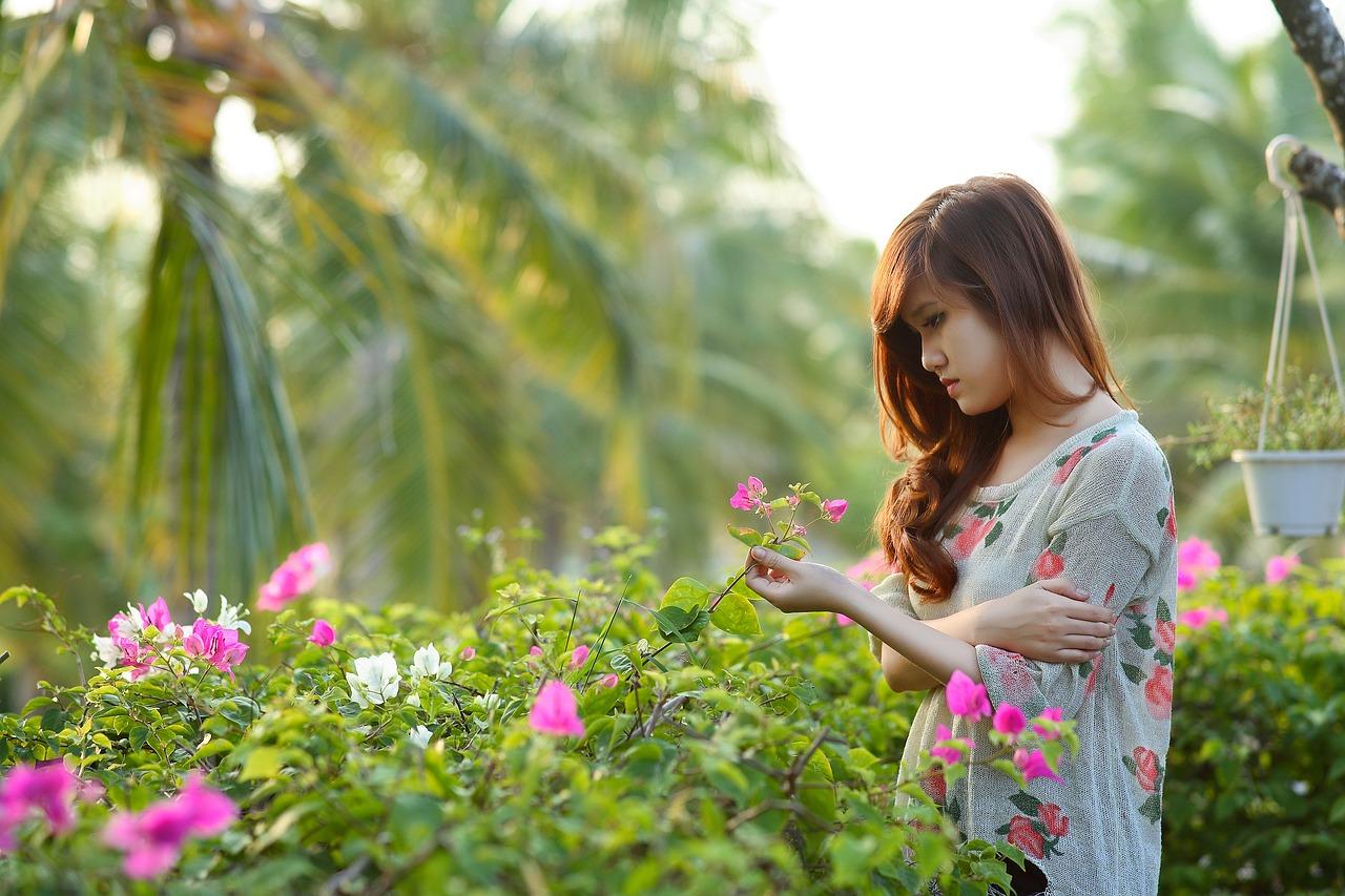 Jeune fille contemple une fleur dans jardin