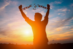 87173291 - silhouette image of a businessman with broken chains in sunset