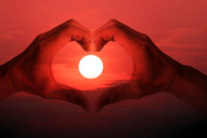 double exposure of hand made heart symbol across the sun was falling.
