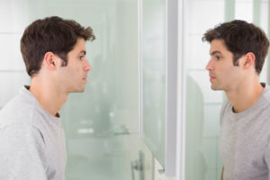 side view of a tensed young man looking at self in mirror in the bathroom