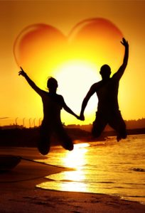 13077536 - happy young couple jumping, holding hands with heart shape in the sky, symbol of happiness, family playing outdoor, sunset on the beach, fun romantic honeymoon vacation, love concept